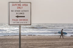 Beach Sign at Virginia Beach Oceanfront With surfer. Beach sign on the Virginia Beach oceanfront with surfer in the background walking in the opposite direction Royalty Free Stock Photography