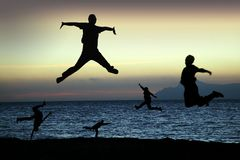 Beach silhouettes jump for joy. Silhouettes of five people jumping for joy, set against a beach sunrise/sunset Royalty Free Stock Photography