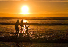 Beach Silhouettes at Sunset 1. With the sun setting, a young people are playing at the beach on the Oregon Coast Royalty Free Stock Image