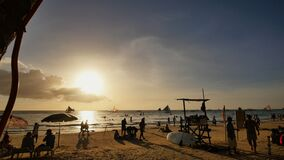 Beach with silhouettes of tourists among palm trees on the island of Boracay. Palm trees in the rays of sunset