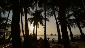 Beach with silhouettes of tourists among palm trees on the island of Boracay. Palm trees in the rays of sunset. Sailboats on the water. Philippine Tropics stock video