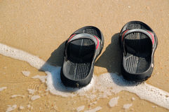 Beach Slippers. Rubber slippers in the wave foam on the beach Stock Images