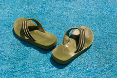 Beach slippers. Green beach slippers on a blue background Stock Photo