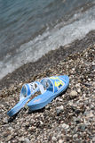 Beach slippers. Blue beach slippers ashore on pebble. Waves on a background Stock Images