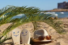 Beach slippers with painted happy faces and a hat with sunglasses under palm leaves on the sand near the sea.  Royalty Free Stock Images