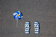 Beach slippers with pinwheel lying on asphalt Stock Image