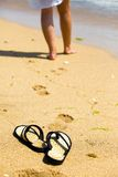 Beach slippers on sand and female feet Royalty Free Stock Photos