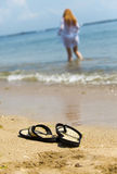 Beach slippers on sand and girl in ocean Royalty Free Stock Photo