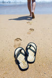 Beach slippers on sand and girl in ocean out of fo Royalty Free Stock Photography
