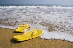 Beach slippers on a sandy beach Stock Photos