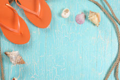 Beach slippers, seashells and rope on the background of painted Stock Image