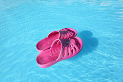 Beach slippers swimming on water in pool Royalty Free Stock Image