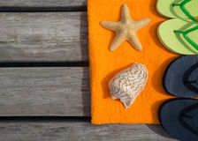 Beach slippers, towel and starfish on wood background Stock Photos