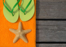 Beach slippers, towel and starfish on wood background Stock Photo