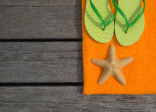 Beach slippers, towel and starfish on wood background Royalty Free Stock Photos