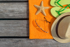 Beach slippers, towel and sunglasses on wood background. Royalty Free Stock Images