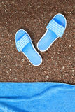 Beach slippers and a towel to lie on a pebble beach. Royalty Free Stock Photos