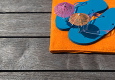 Beach slippers, towel on wood background. Concept of leisure Stock Photos