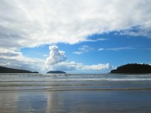 Beach with small waves on blue sky day and clouds. Beach with small waves in blue sky day and clouds, with islands on the horizon Stock Photos