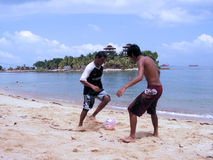 Beach soccer at beach resort. Asian friends playing beach soccer. Location is Sentosa Island Resort in Singapore Stock Images