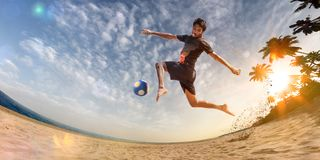 Beach soccer player in action. Sunny beach wide angle. And sea royalty free stock photos