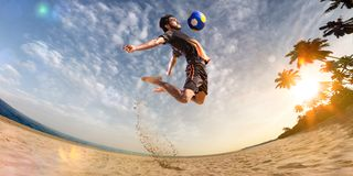 Beach soccer player in action. Sunny beach wide angle. And sea royalty free stock photography