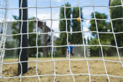 Beach soccer player through the net. Rio olympic games. Royalty Free Stock Photo