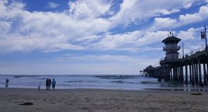 Beach with some people, next to a pier with a lighthouse. Beautiful and quiet beach with some people watching the waves, next to a large wooden pier with a small royalty free stock images