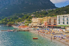 Beach, Amalfi Coast, Italy. Colorful umbrellas and lounge chairs line the cobblestone beach full of people at the picturesque village of Marina del Cantone, on stock image