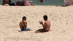 Beach in Sousse, Tunisia. TUNISIA, SOUSSE, JULY 7, 2010: Two Tunisian boys eat on the beach in Sousse, Tunisia, July 7, 2010 stock video footage