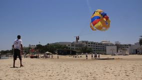 Beach in Sousse, Tunisia. Parasailing, also known as parascending, or parakiting is a recreational kiting activity where a person is towed behind a vehicle ( stock footage