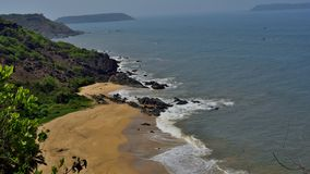 Beach in South Goa, hill on one side and island on other. A scenic beach in south Goa, India. It has hills on one side of the beach with visible islands stock photography