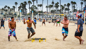 Beach Spikeball. Four friends playing America's next great sport which mixes the fun of volleyball with foursquare Royalty Free Stock Image
