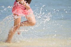 Beach splash. Female running along a sandy beach, splashing in the waves Stock Photography