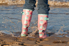 Beach Splash Time. A girl in Wellington boots splashing in the sea at the beach Stock Photography