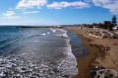 Beach of St. Augustin, Gran Canaria. Africa. Some tourists are sunbathing. Sky is blue, sun is shining and there are some white clouds. In the front there are Royalty Free Stock Photo