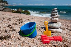 Beach with stacked stones and toys Stock Images