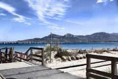 Beach. Stair, bridge, passage to the beach, yellow sand, blue sky, people on the beach, boats on the blue sea, mountains, blue sky, clouds Stock Image