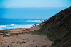 Beach and the stairs. Stairs to the beach. Beautiful waves and the sand. Barwon Heads, Victoria, Australia. Another shore on the background stock photos