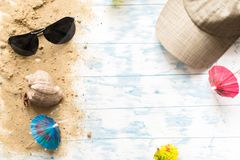 Beach still life. Black glasses with cocktail umbrellas, seashell on sand on a wooden background Royalty Free Stock Photos