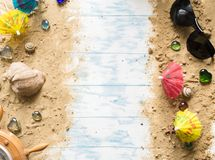 Beach still life. Black glasses with cocktail umbrellas, seashell on sand on a wooden background Stock Image