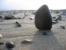 Beach stone. A stone stands upright in the sand, silhouetted against the beach, casting a shadow directly towards the camera Royalty Free Stock Photo