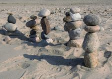 Beach stone figures marching off into the distance. These stone figures were found on the beach if E. Sandwich, MA. They were asembled at the oceans edge, likely Stock Images