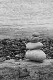 Beach stones. Stacked stones on a weathered log at the waters edge stock photos