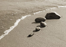 Beach stones. Five stones on the sand, meeting the sea wave. Sepia toned image Stock Image