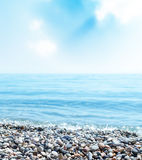 Beach with stones, sea and blue sky with clouds Stock Photo