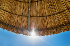 Beach straw parasol umbrella against blue sky Stock Photo