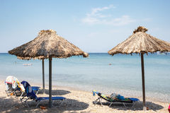 Beach with straw sun umbrellas and sunbeds. Stock Photo