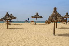 Beach with straw umbrellas and beds stock photos