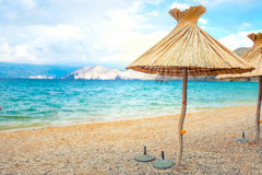 Beach straw umbrellas lounger chair with sand and clear water Stock Image